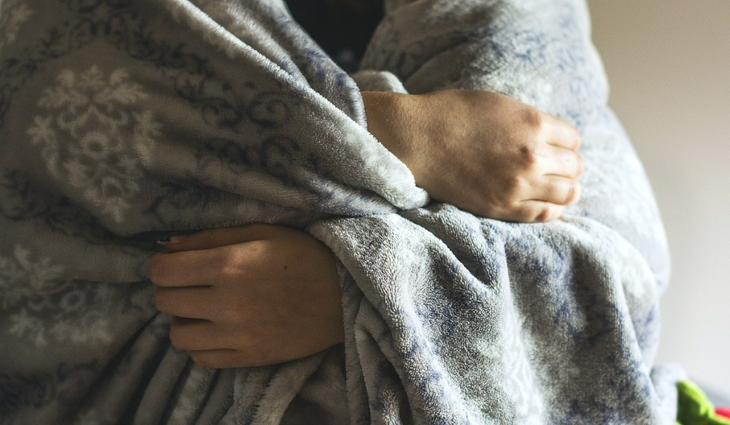 person holding blanket around themselves