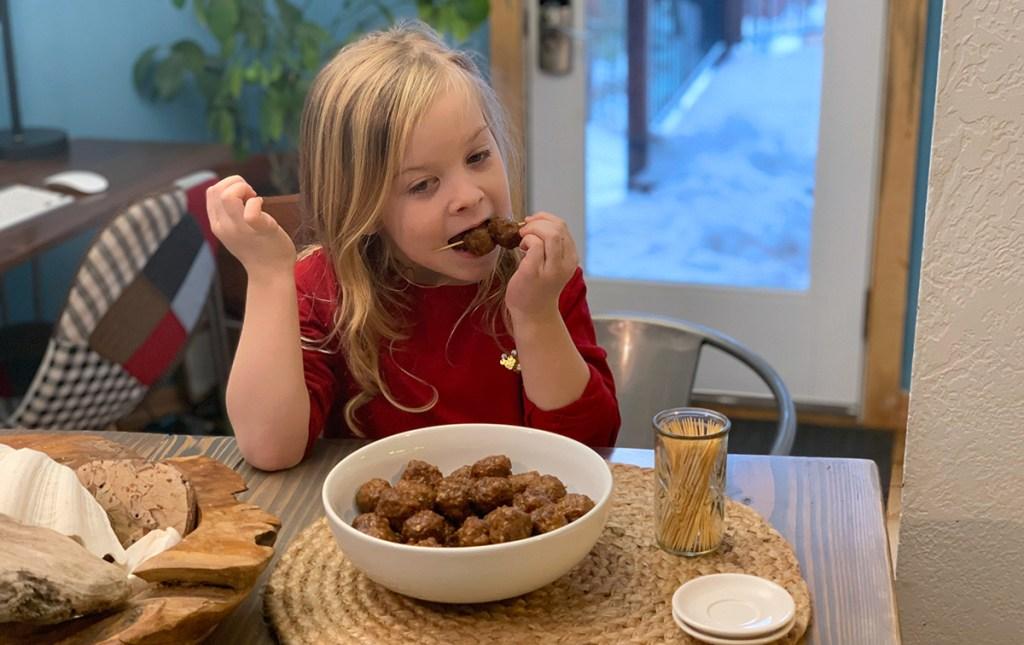 young girl eating meatballs