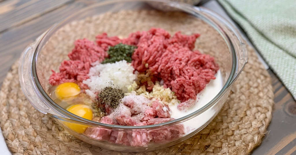 bowl with ground beef and other ingredients for meatballs
