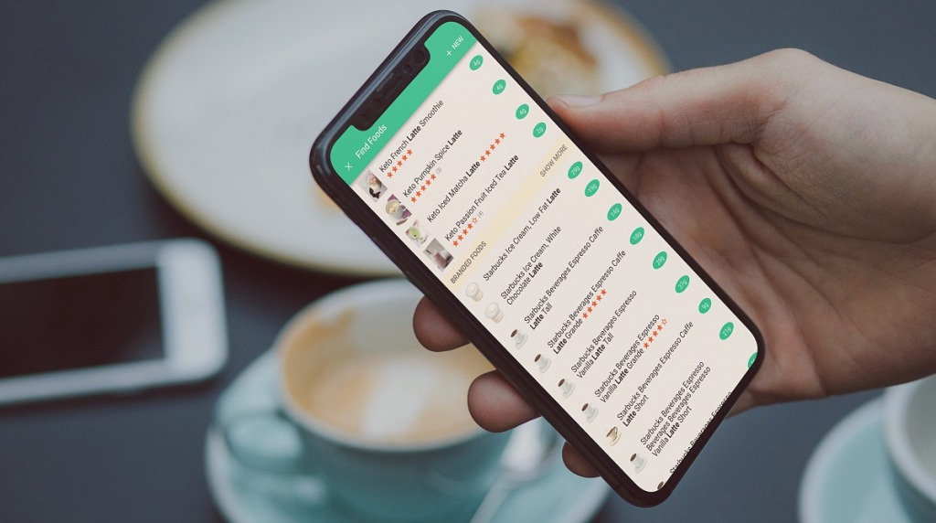 hand holding iphone with keto latte listings on carb manager