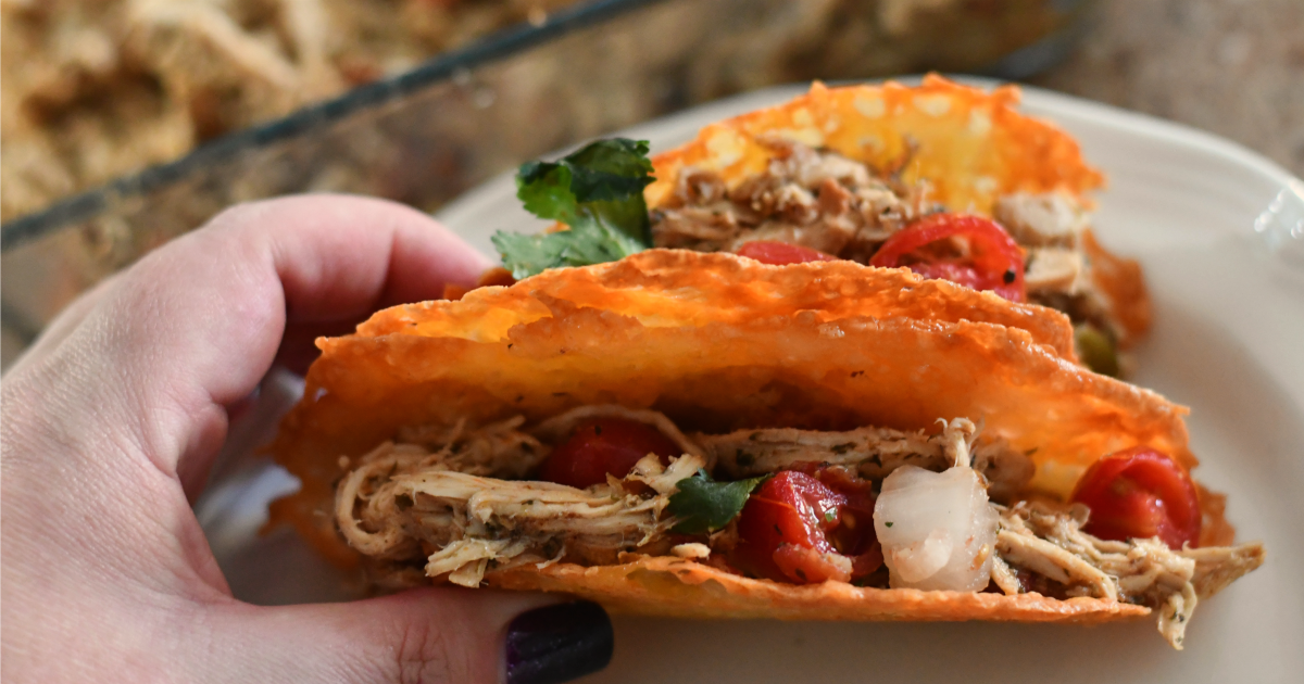 Keto Slow Cooker Shredded Chicken Tacos - a hand holding a delicious shredded chicken taco in a crispy cheese shell