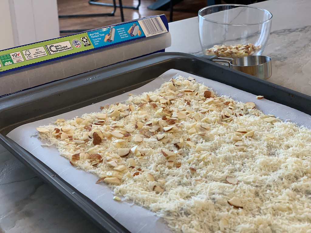 shredded cheese and almonds on pan with parchment paper
