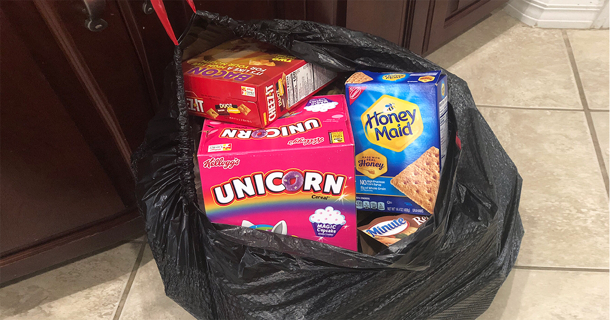 garbage bag filled with cereal, crackers, and other non-keto food