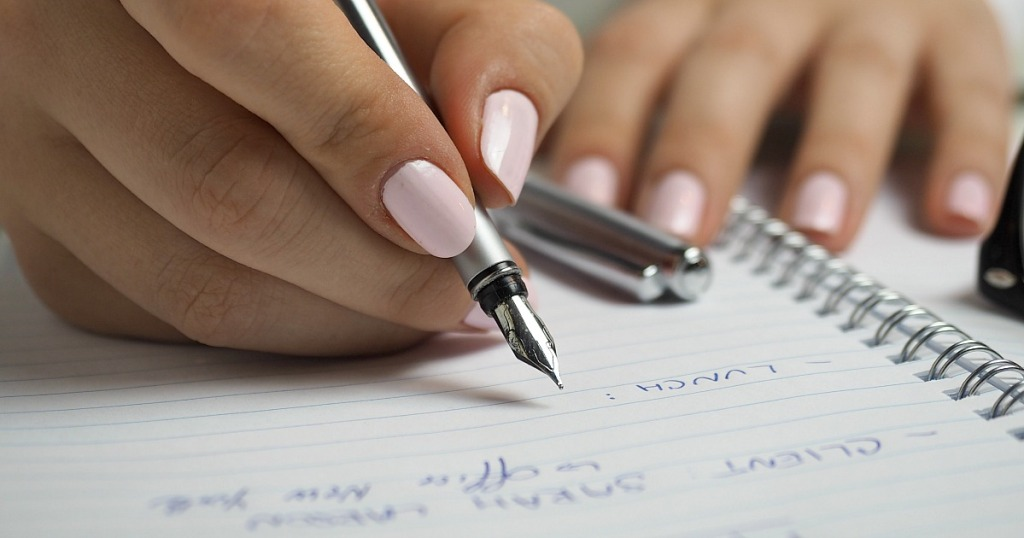 woman writing down lunch plans in notebook
