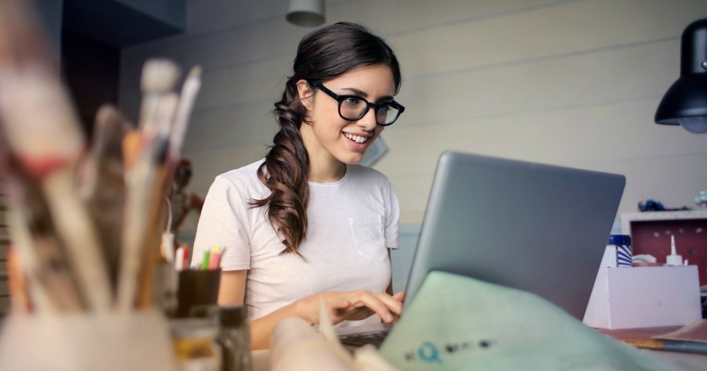 woman wearing glasses sitting focused at computer