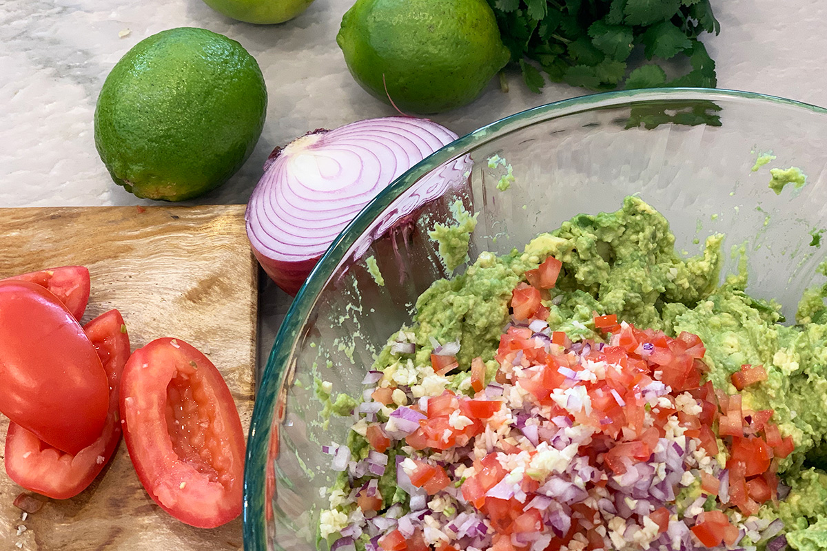 mixing together the guacamole ingredients in a bowl