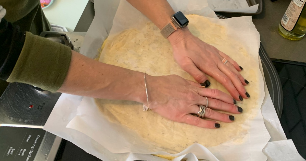 woman pressing down fathead dough with parchment paper