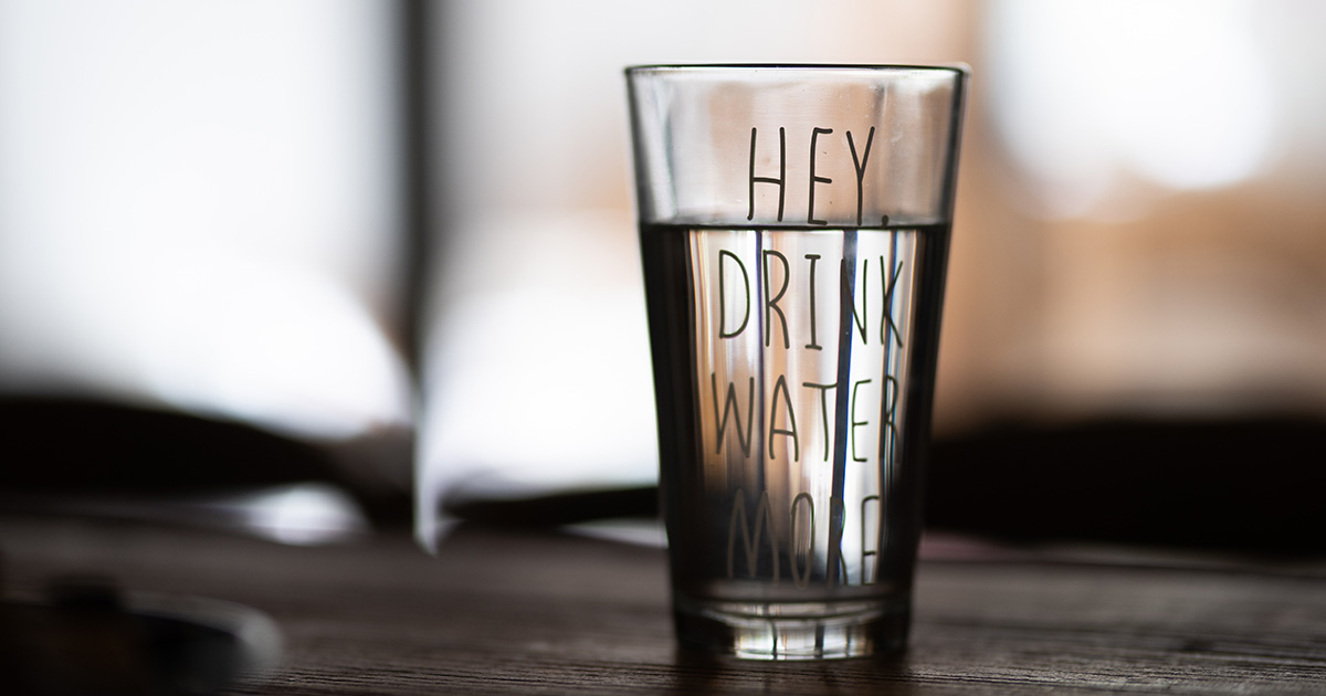 a glass of water that says Hey, Drink Water More