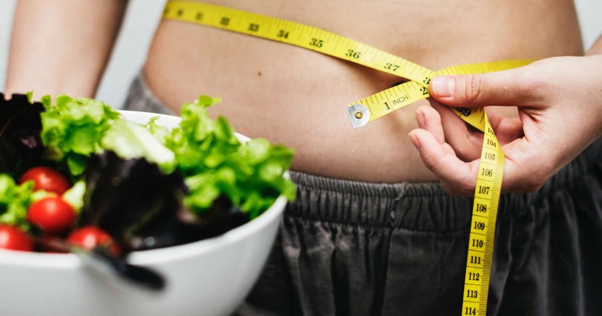 a woman holding a measuring tape around her waist near a salad