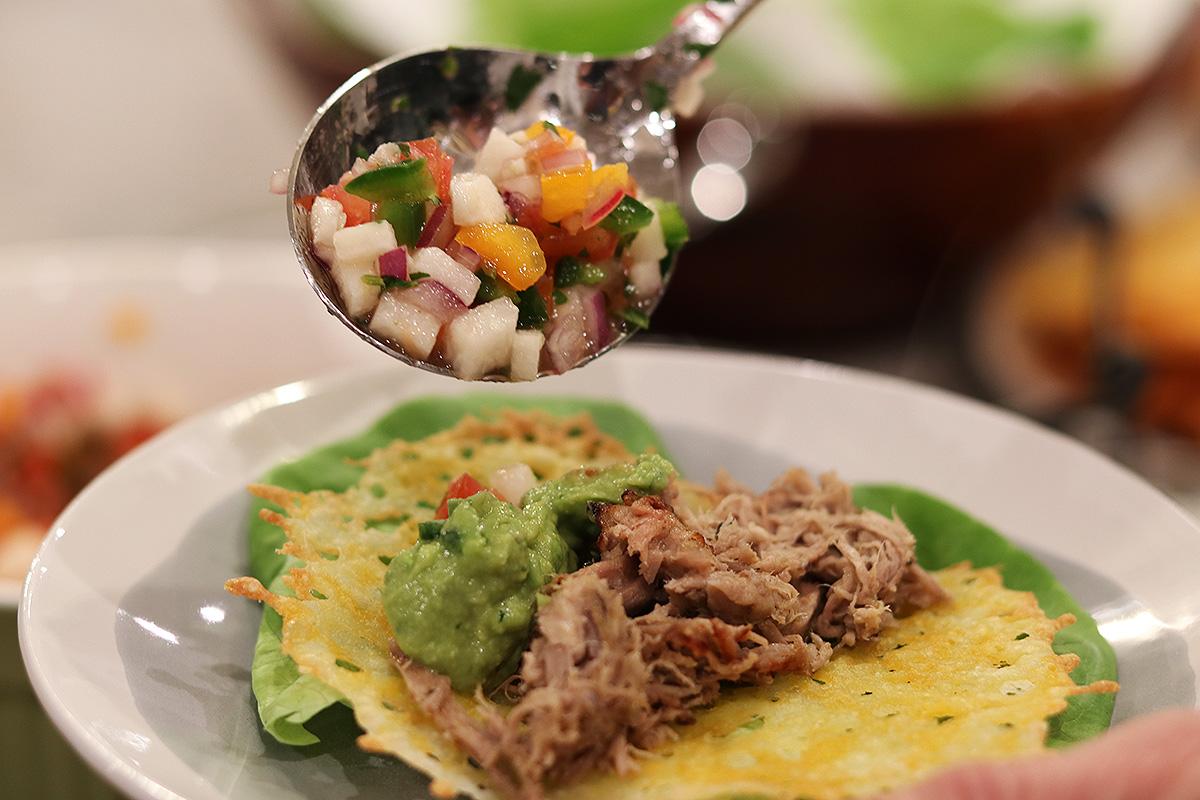 spooning pico de gallo on cheese shell tacos
