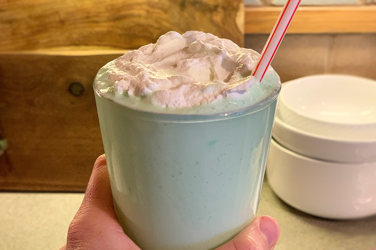 a hand holding a large keto shamrock shake with whipped cream