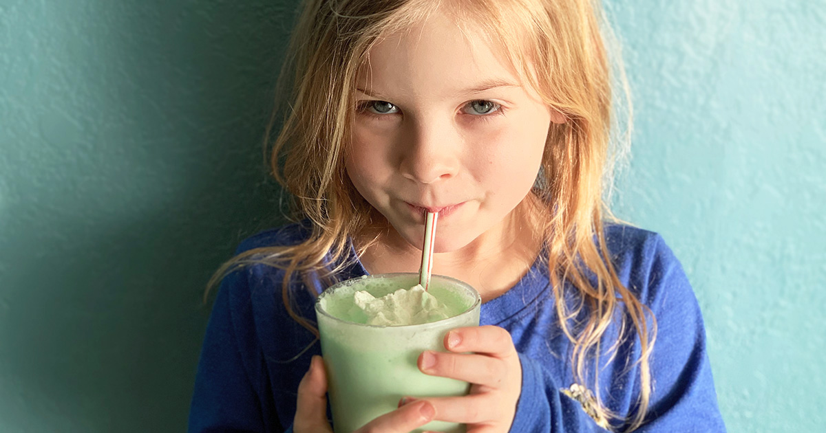 a young girl sipping the keto shamrock shake copycat recipe through a straw