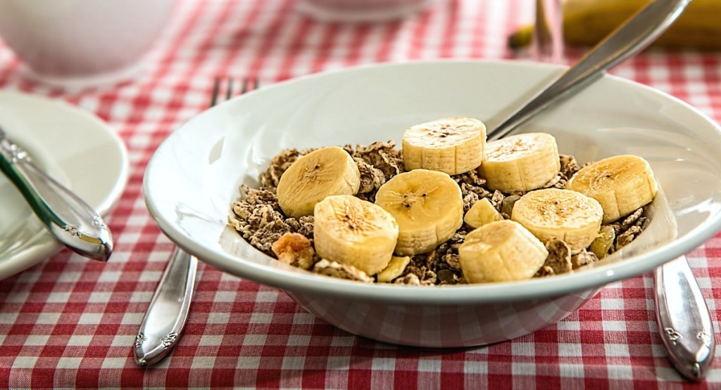 bowl of granola cereal with sliced banana