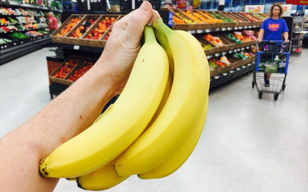 holding up bunch of yellow bananas