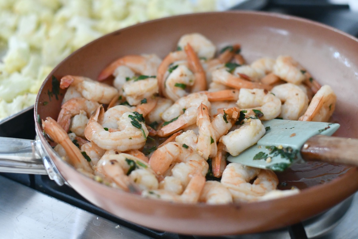 mixing herbs with shrimp in the pan