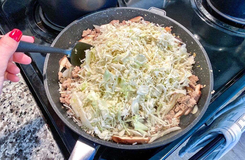 adding shredded cabbage to pan for keto egg roll in a bowl