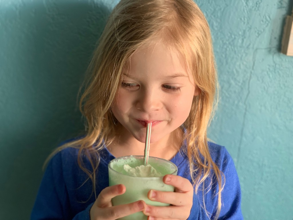 little girl drinking keto shamrock shake