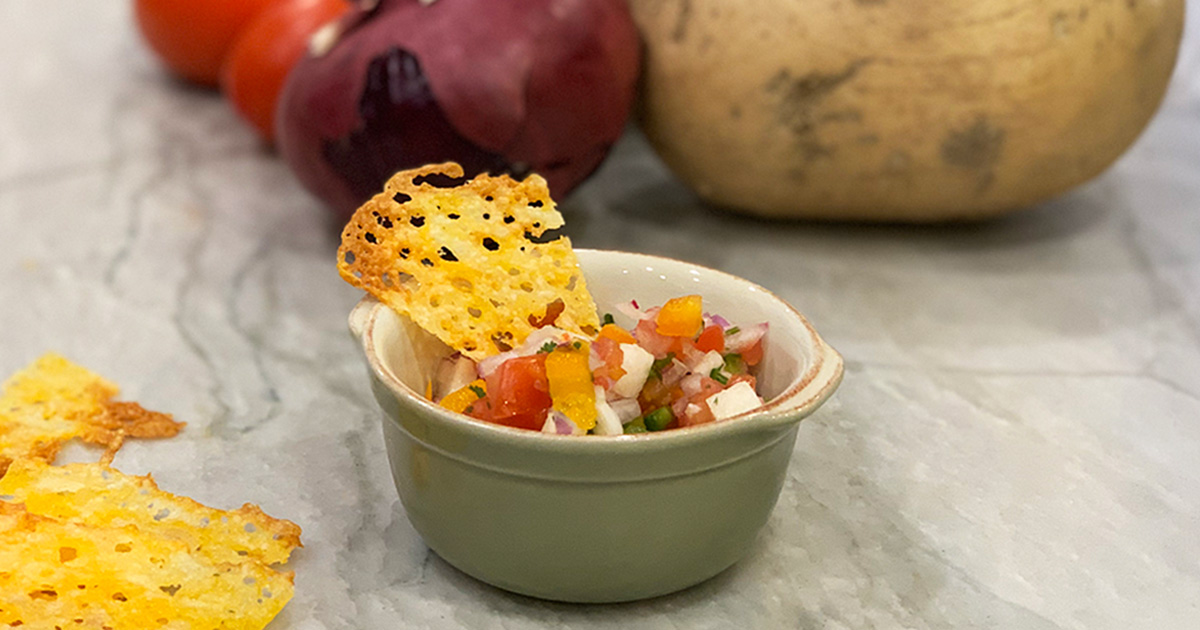 baked cheese chip dipped into the pico de gallo