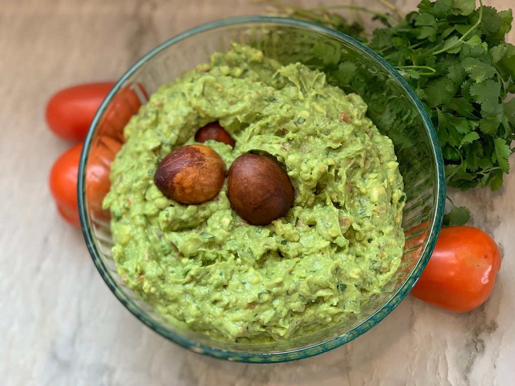 freshly prepared guacamole in large glass bowl