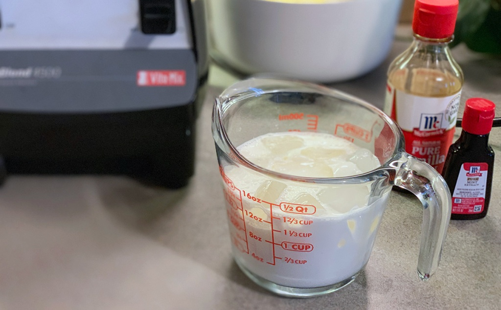 measuring cup with heavy cream and bottles of vanilla and peppermint extract