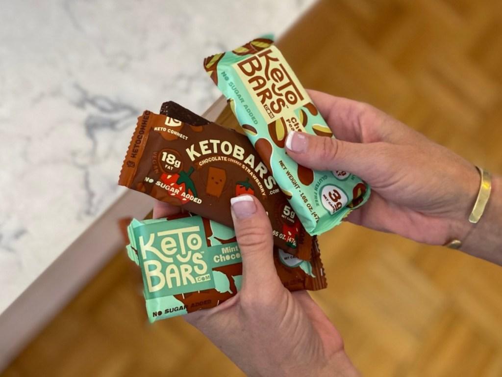 holding 3 Keto Bars in kitchen