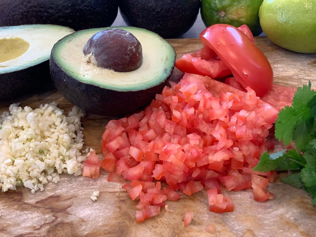 avocado, diced tomatoes and minced garlic on cutting board