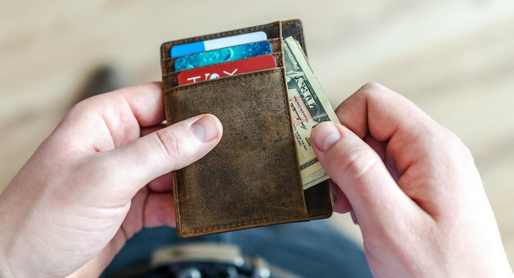 pulling cash out of wallet with bills and credit cards