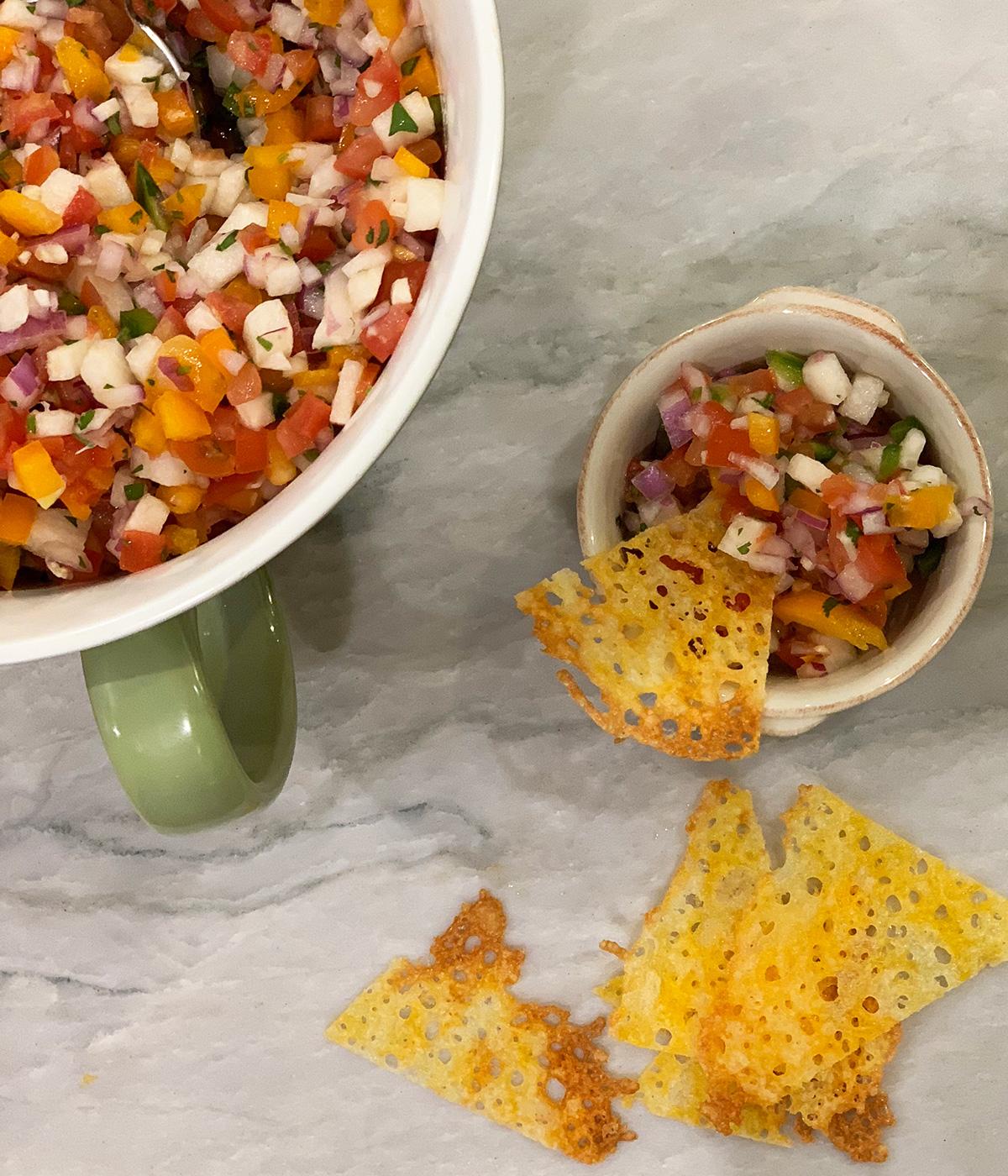 a small ramekin of pico de gallo next to a larger serving bowl