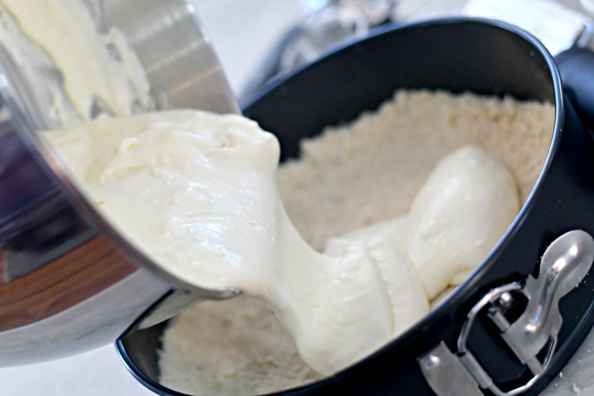 pouring the cheesecake batter into a springform pan