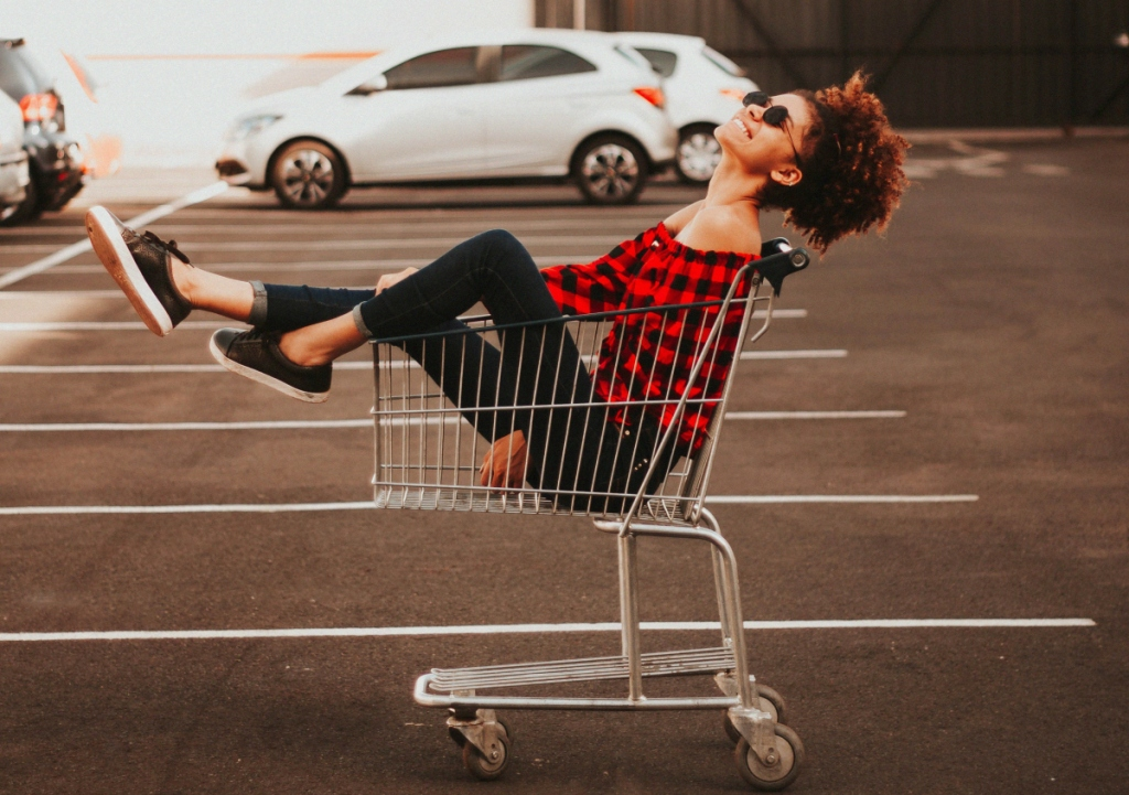 woman sitting in shopping cart