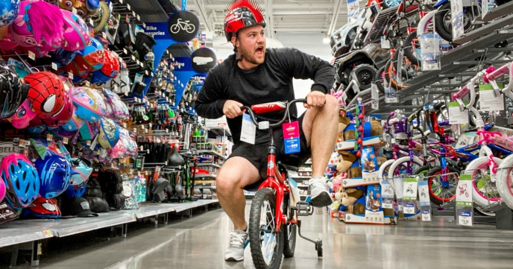 man in bike section of the store on a tricycle
