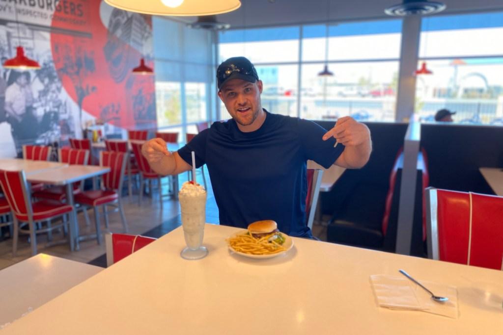 man at Steak n' Shake with burger, fries, and milkshake