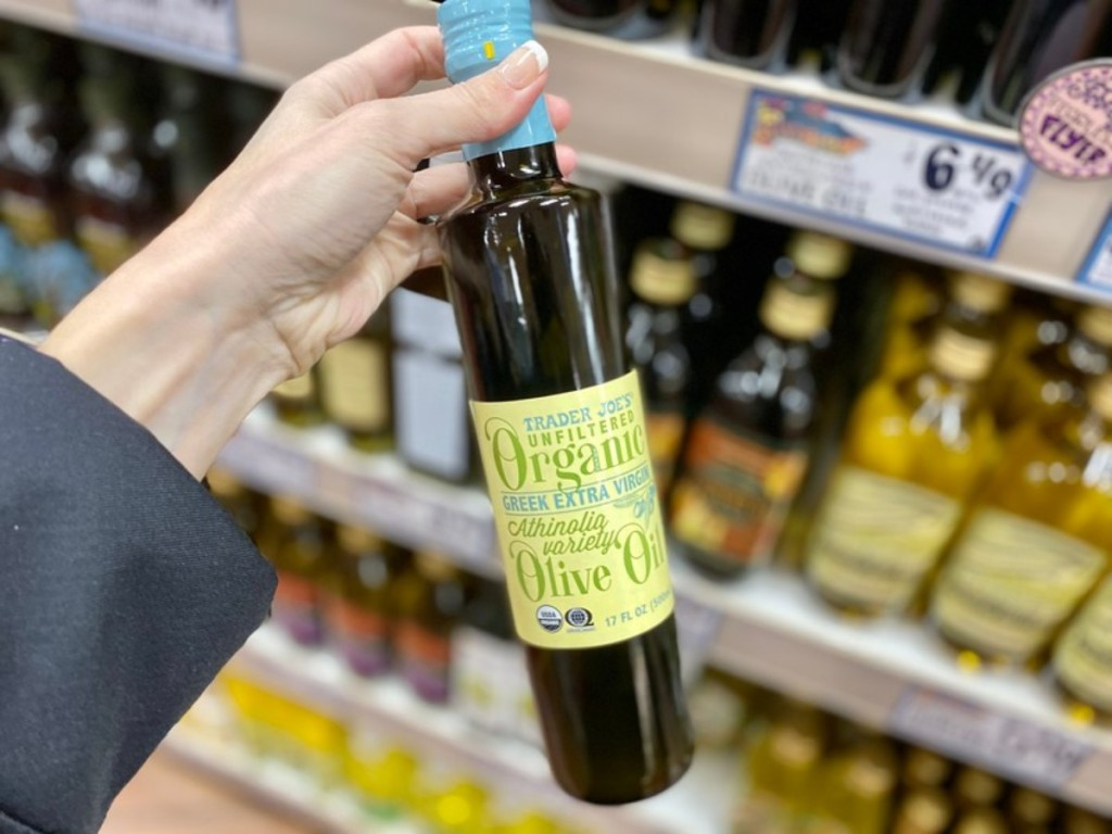 holding bottle of olive oil at Trader Joe's