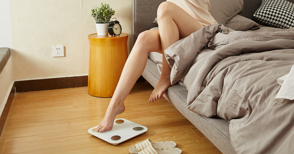 woman stepping out of bed onto scale