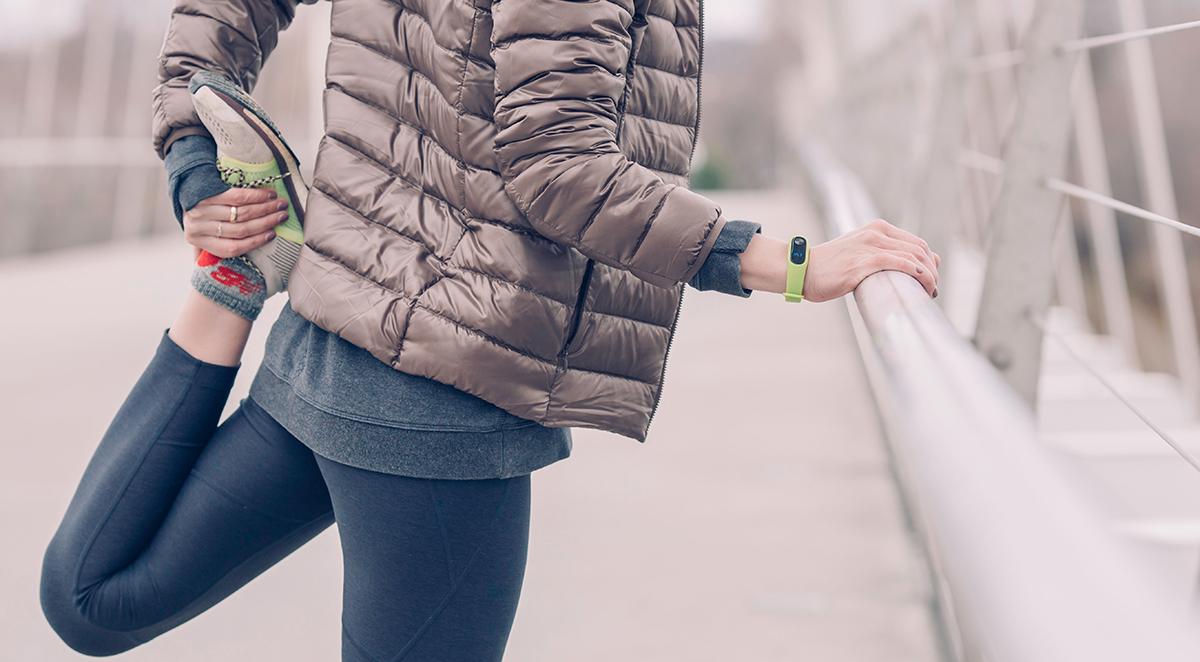 woman in athletic gear stretching on sidewalk