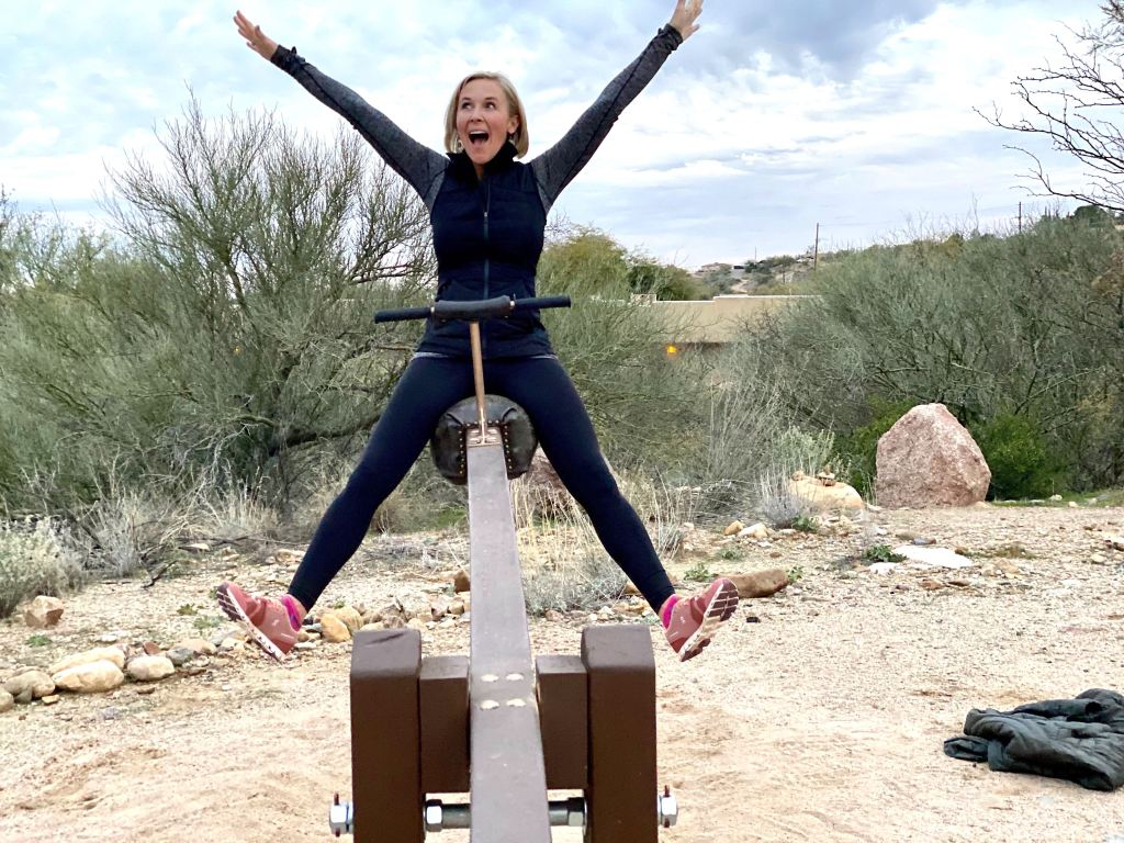 woman with arms up and excited on see-saw
