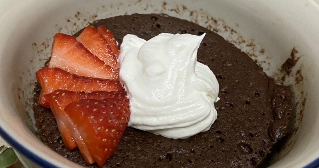 keto chocolate mug cake with strawberries and whipped cream