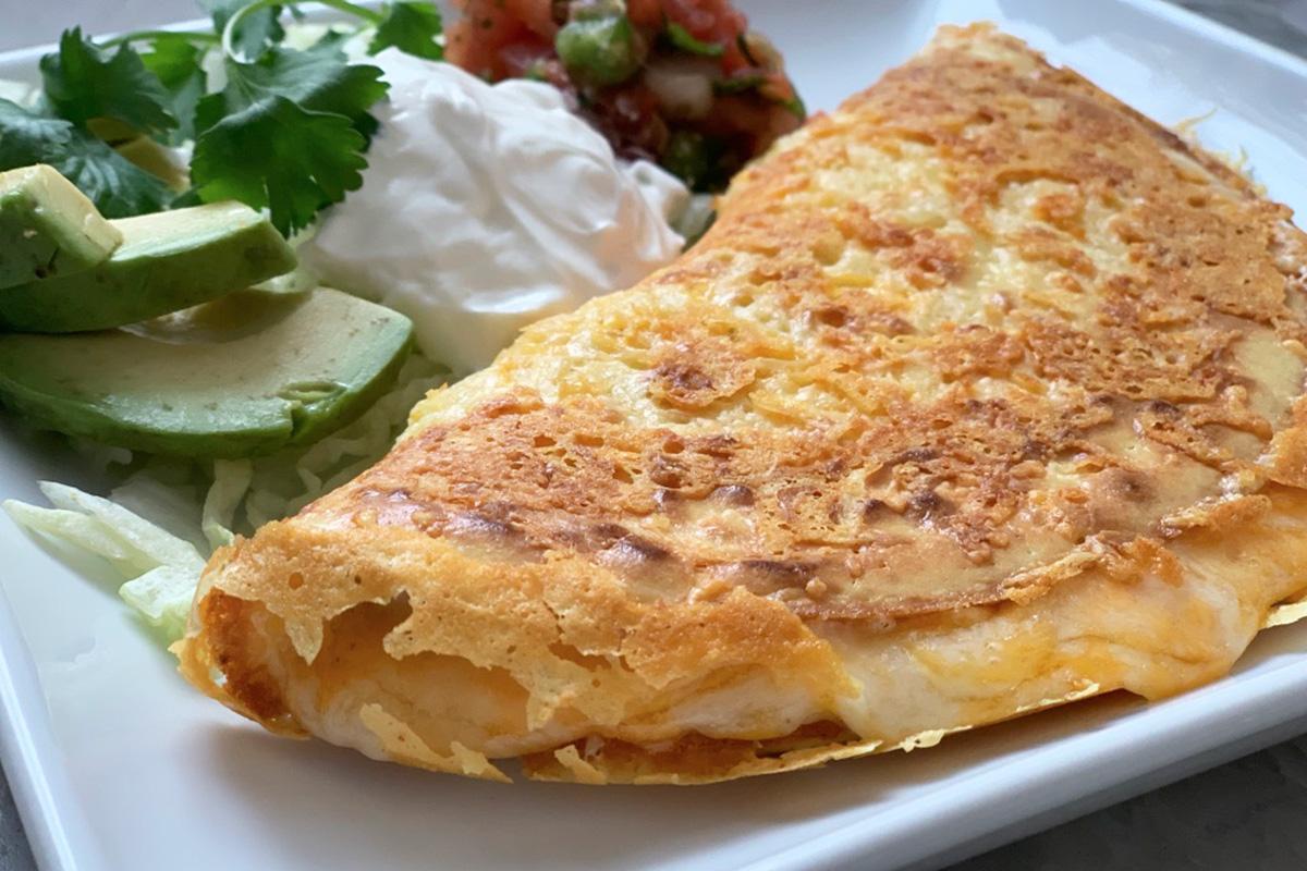 a plate with a keto quesadilla along with avocado sour cream and pico de gallo