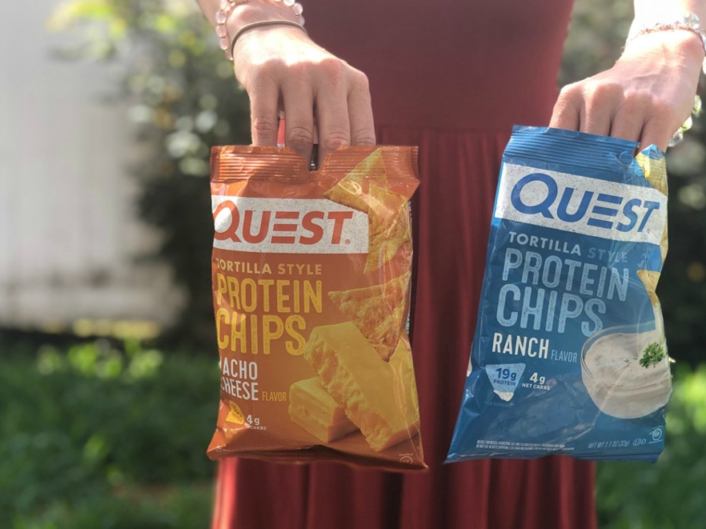 woman holding two bags of Quest tortilla style protein chips