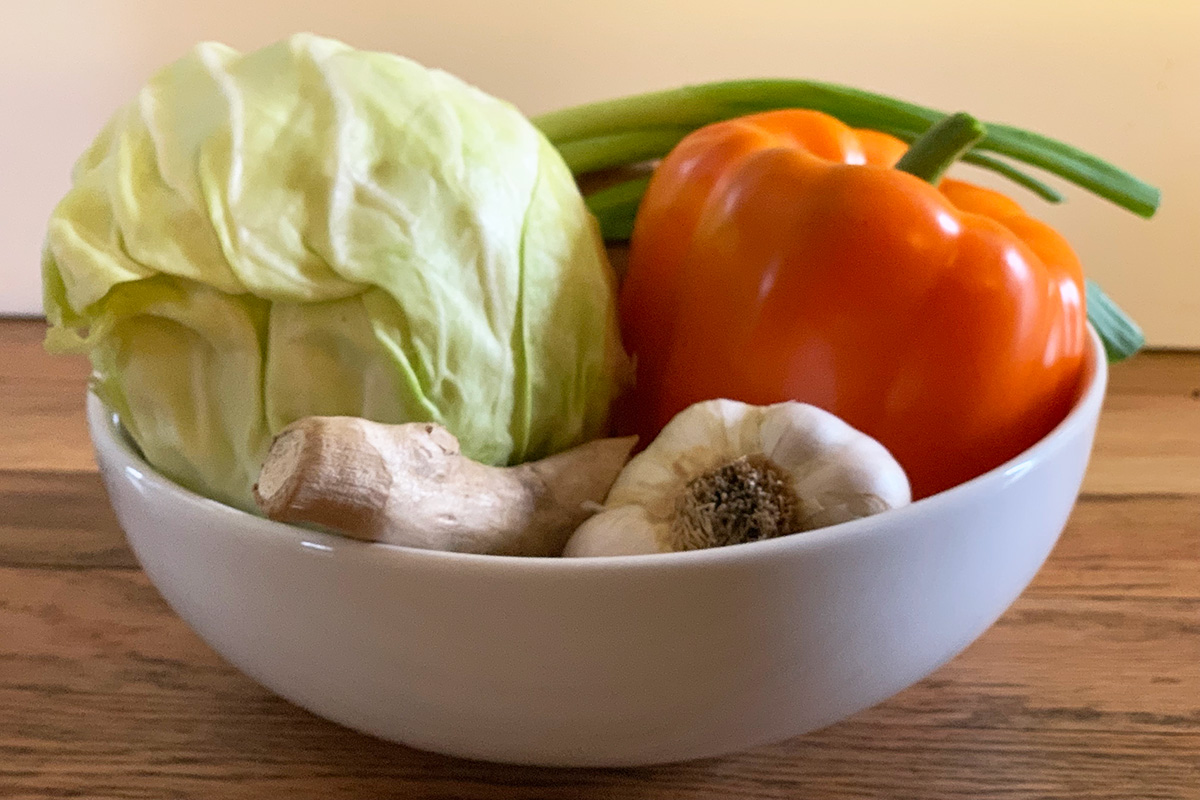 A bow of veggies including cabbage, bell pepper, garlic and ginger