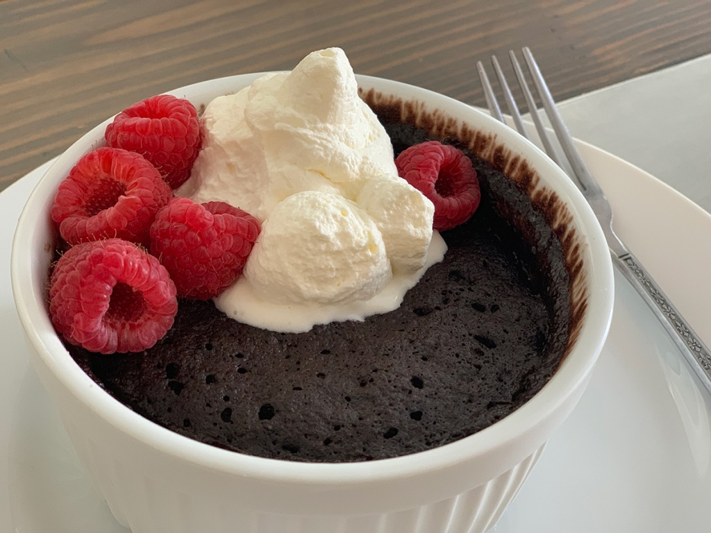 chocolate mug cake with whipped cream and berries