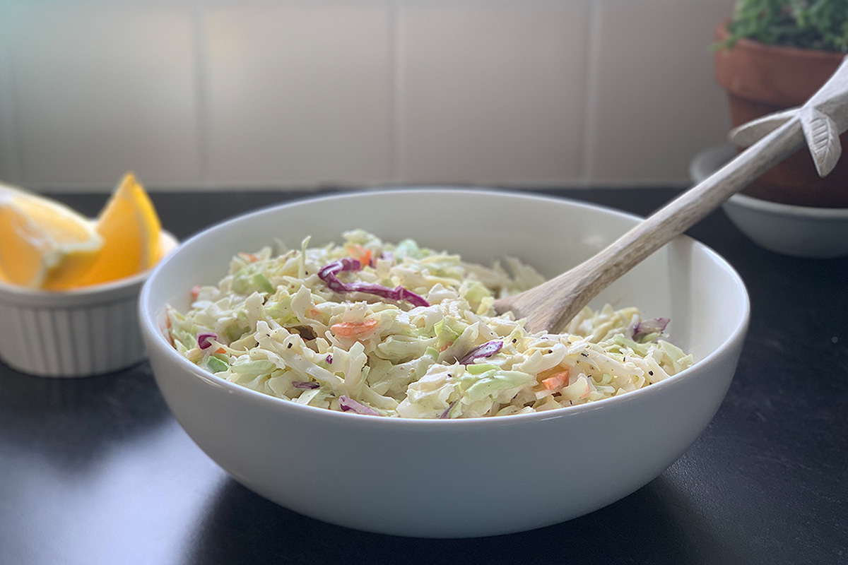 a serving bowl with a spoon ready to dish some low-carb coleslaw