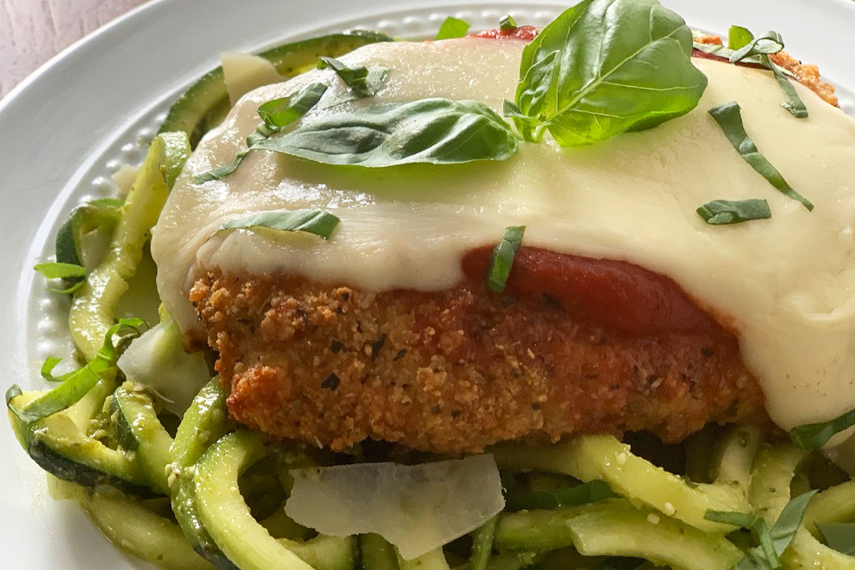 a close up of crispy chicken parmesan with melted cheese and fresh basil