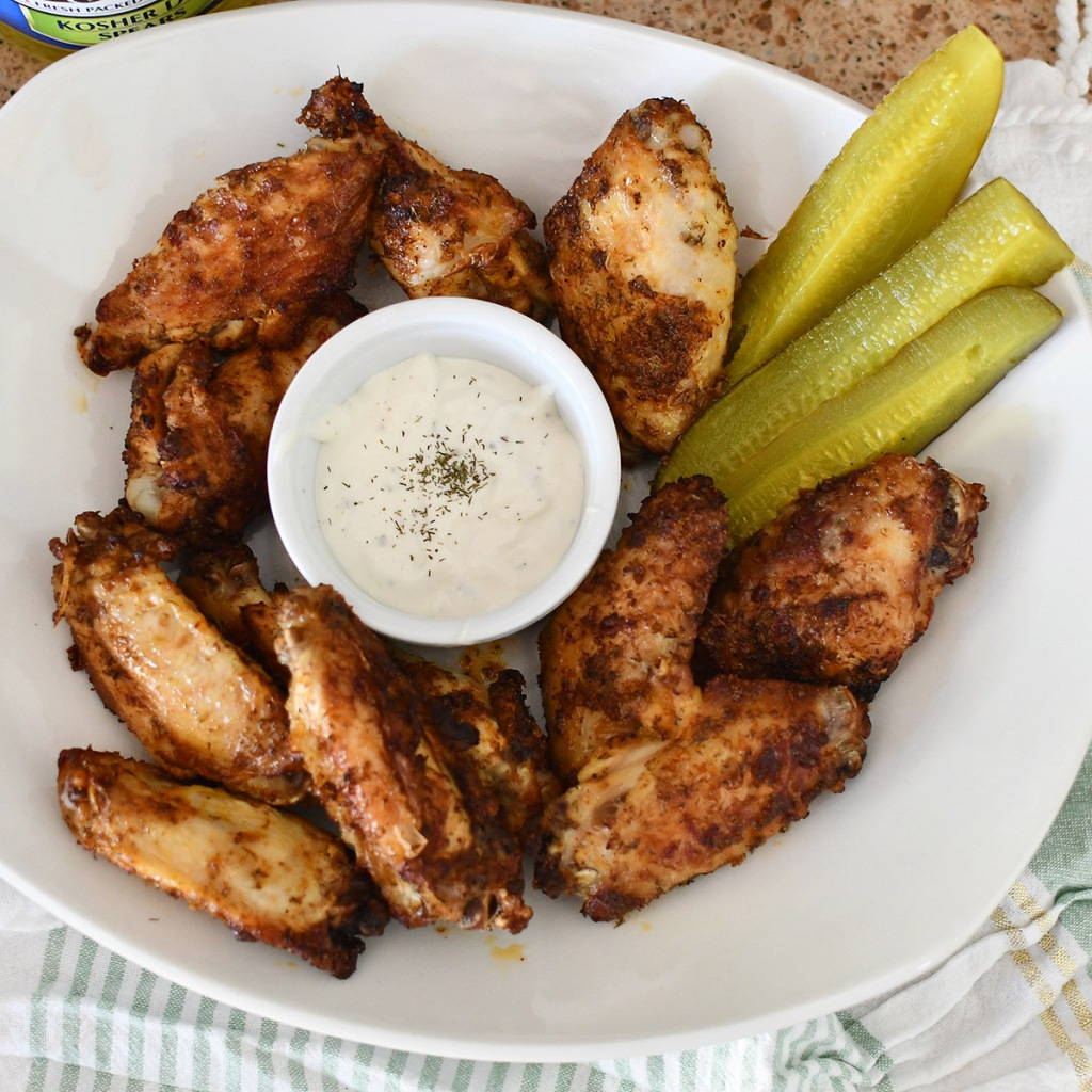plate full of wings with ranch and a pickle