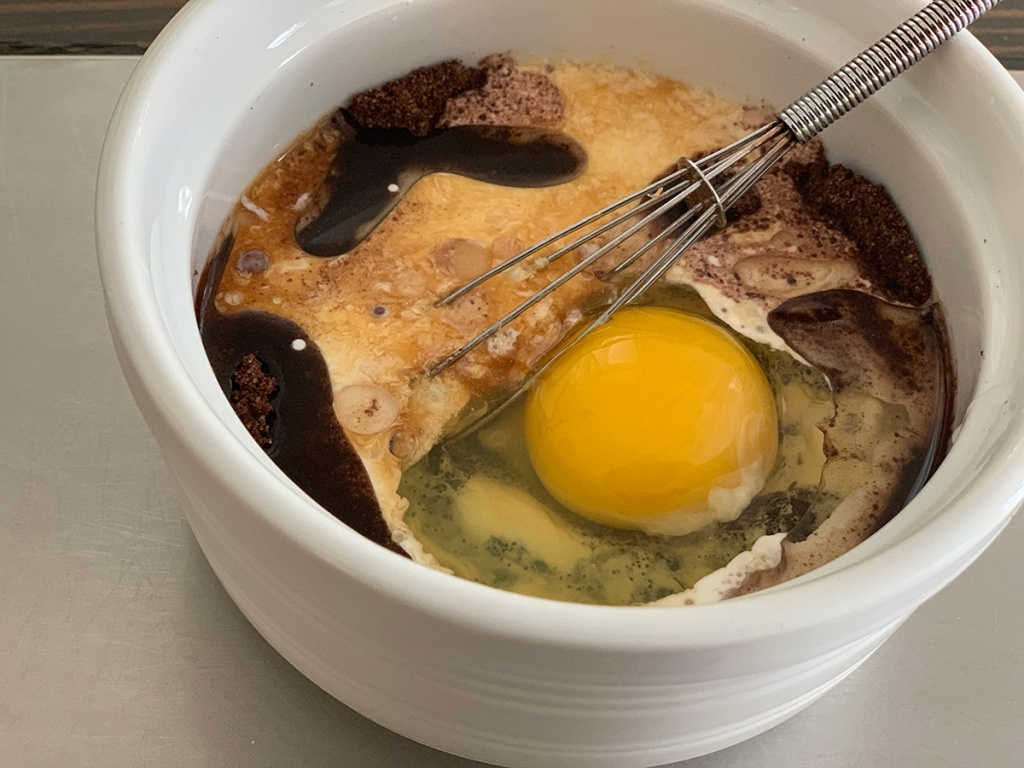 egg mixing into ramekin with mug cake ingredients