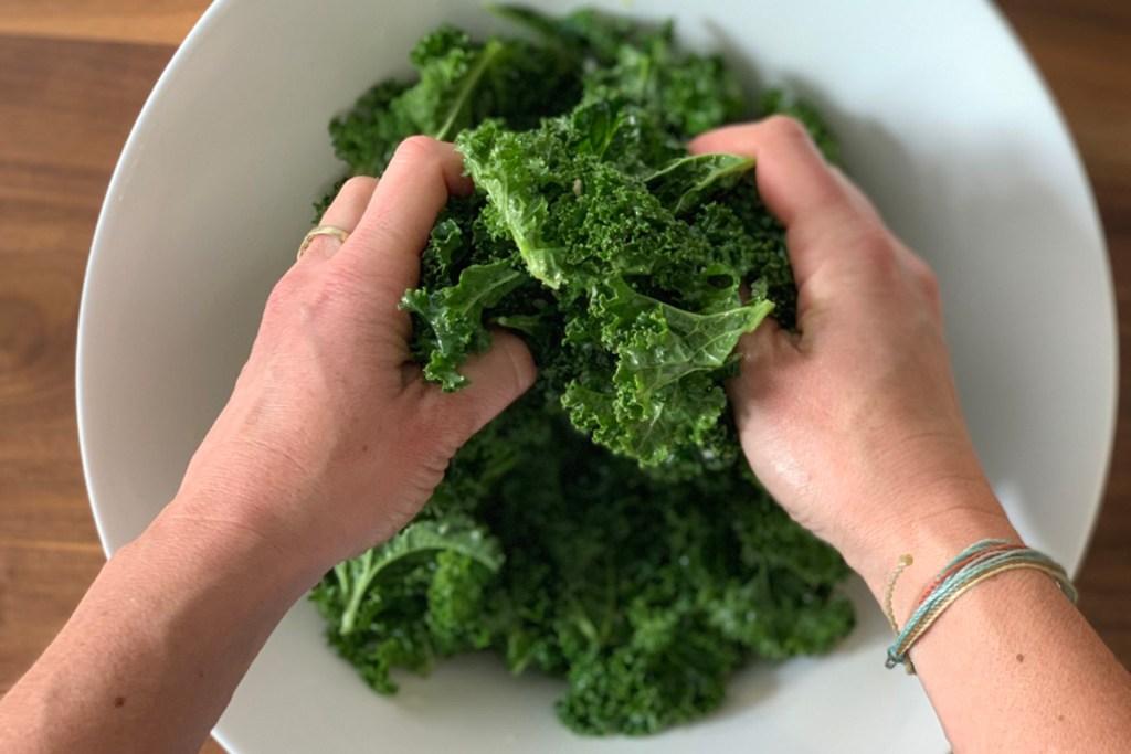 hands massaging kale