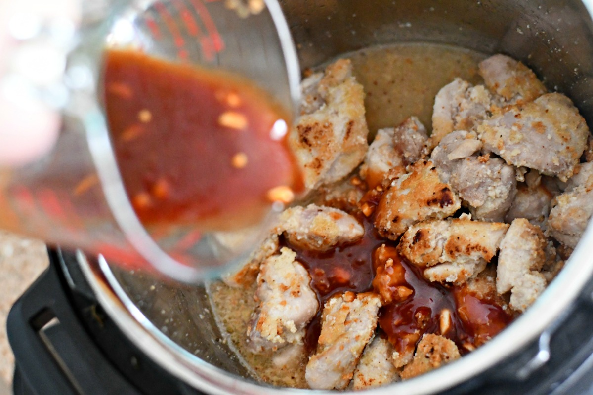 pouring sauce over instant pot chicken before cooking