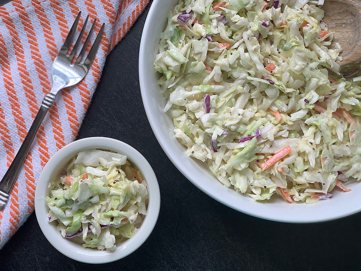 a large bowl of coleslaw next to a small dish of slaw with a fork
