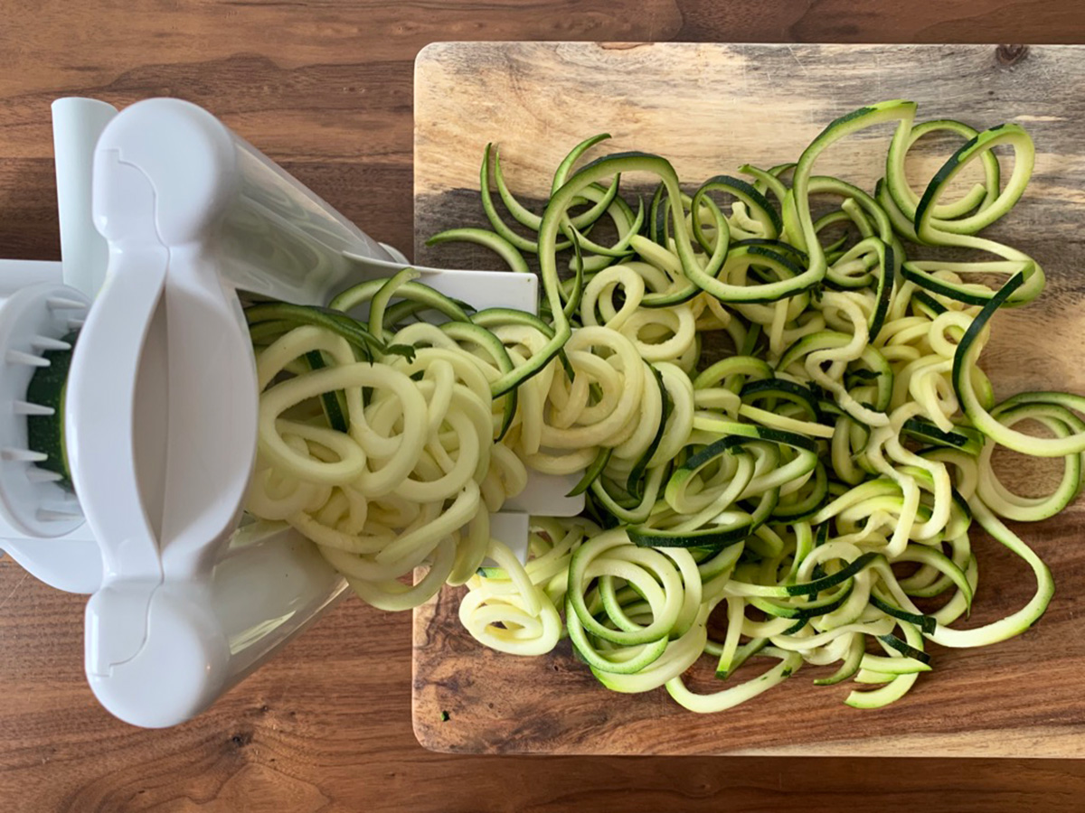 zucchini being spiralized into noodles