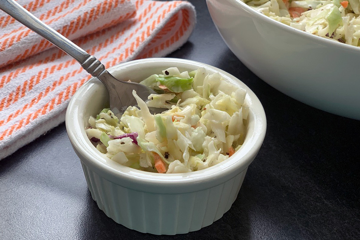a small dish with a fork in the coleslaw